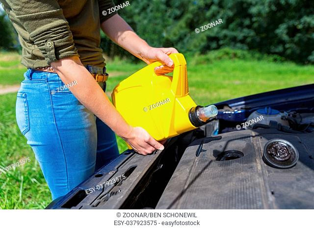Woman filling car motor with oil in jerrycan