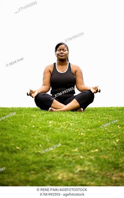 A black plus size female model in Dhyana yoga pose
