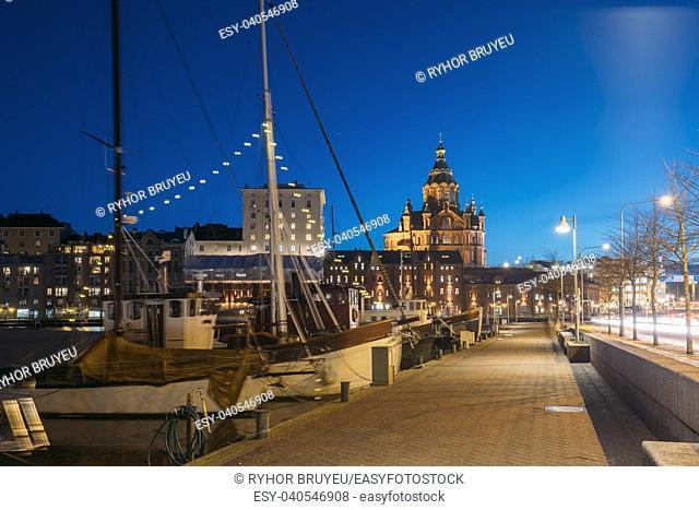 Helsinki, Finland. Pier With Boats, Pohjoisranta Street And View Of Uspenski Cathedral In Evening Night Illuminations