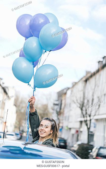 Portrait of smiling woman with blue balloons on the street