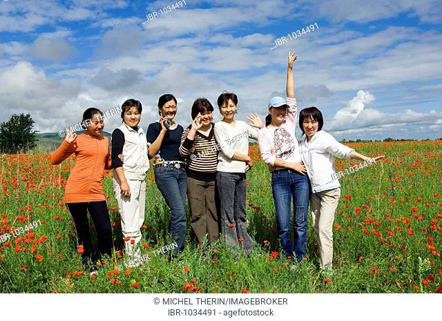 Group of young people in a field of red poppies, Kyrgystan, Central Asia