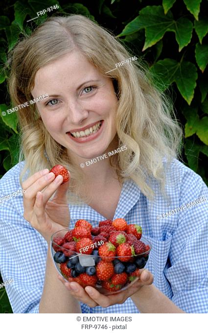 Happy woman holding bowl with fruit