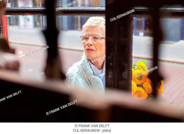 Mature woman with bunch of yellow flowers window shopping