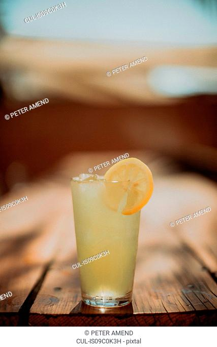 Glass of iced lemon fruit drink on cafe table, shallow focus