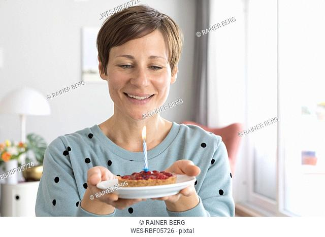 Portrait of smiling woman holding plate with birthday cake