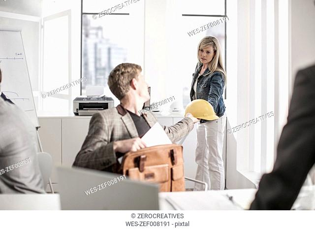 Woman handing over hard hat to colleague in office