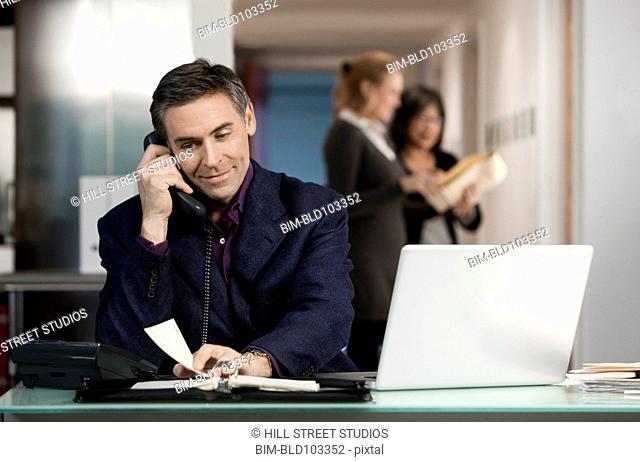 Caucasian businessman using telephone at desk