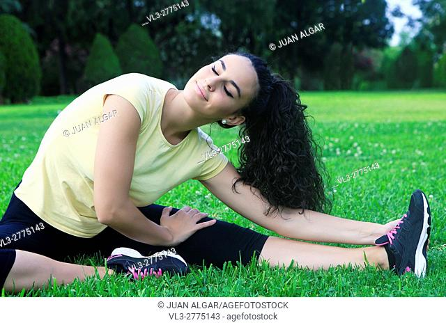 Portrait of beautiful black-haired sportswoman stretching on grass with eyes closed