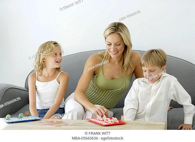 young mother and 2 children is sitting on sofa and are playing a parlour game