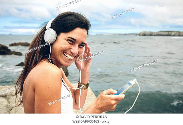 Laughing woman listening music with headphones in front of the sea