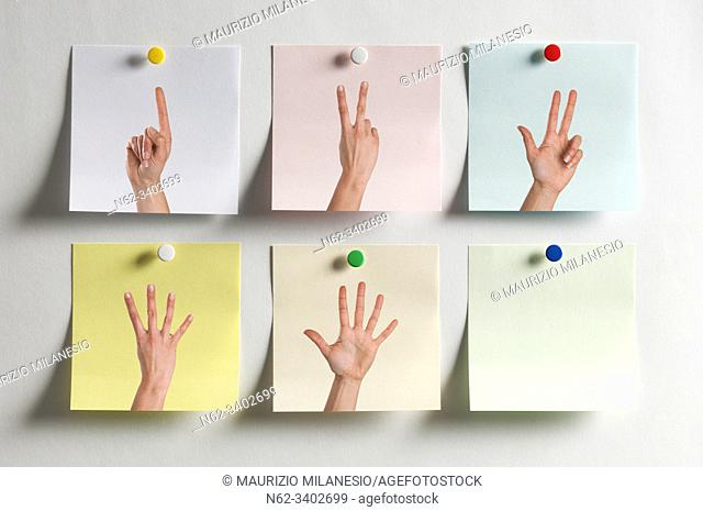 Five colorful Post It messages fixed to the wall with images of fingers indicating numbers and an empty one