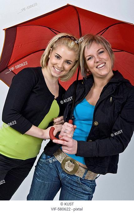 zwei junge Frauen unter rotem Regenschirm - Niederoesterreich, Ísterreich, 26/11/2007