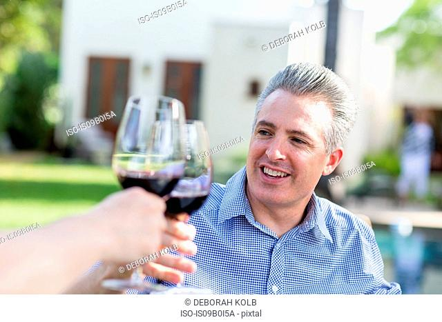 Mature couple making a red wine toast in garden