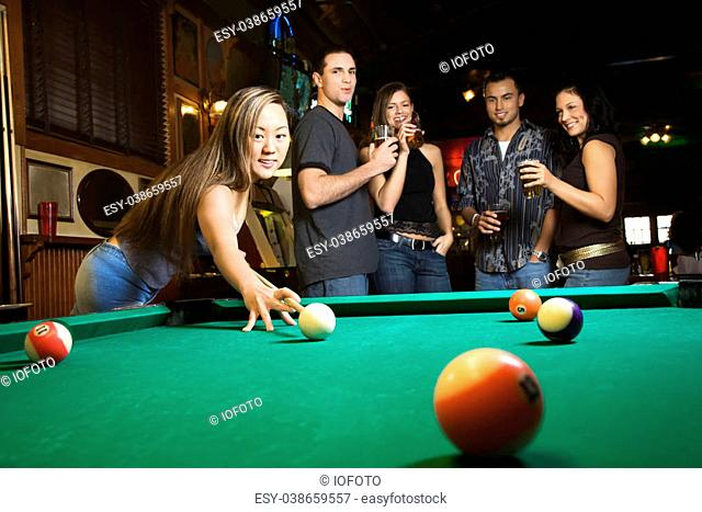 Young asian woman preparing to hit pool ball while playing billiards