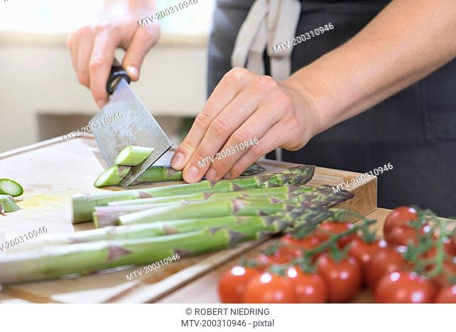 Man cutting asparagus on wooden board