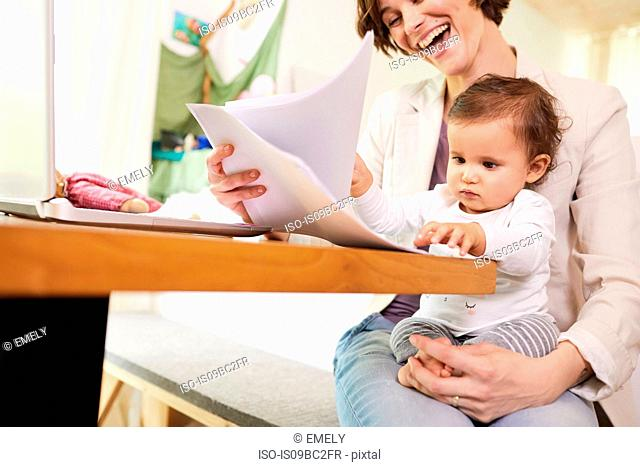 Mother looking at paperwork with baby girl sitting on her lap