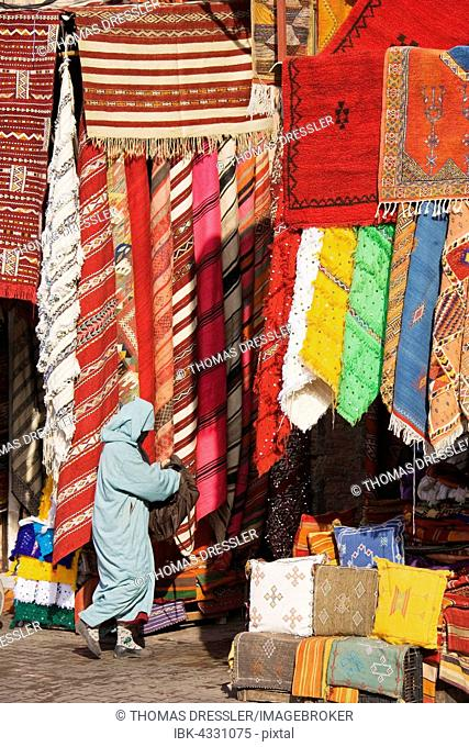 Woman in front of a shop with colourful carpets in the souks of Marrakesh, Morocco