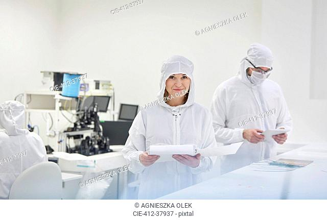 Portrait smiling female engineer in protective suit with paperwork in fiber optics research and testing laboratory