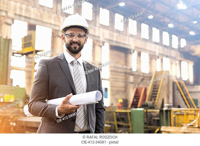 Portrait smiling manager with blueprints in steel factory
