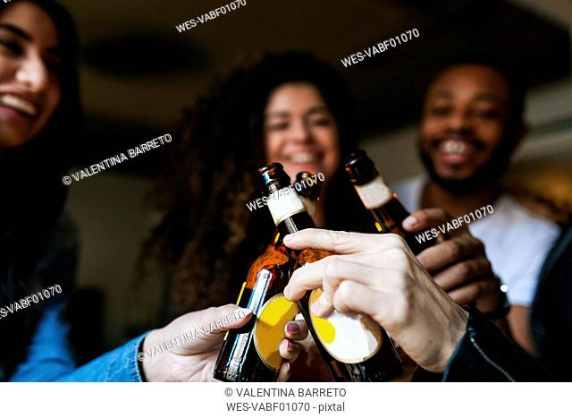 Four friends clinking beer bottles, close-up