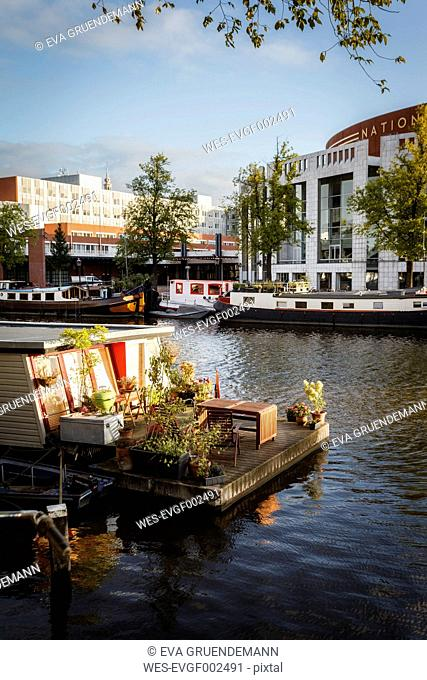 Netherlands, Amsterdam, Houseboat at Amstel river with Het Muziektheater in background