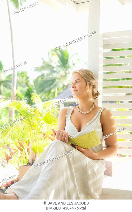 Caucasian woman reading on porch railing