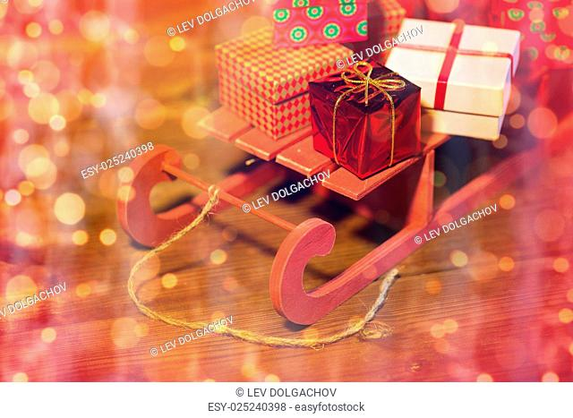 holidays, christmas, presents, new year and celebration concept - close up of many little gift boxes on red wooden sleigh over lights