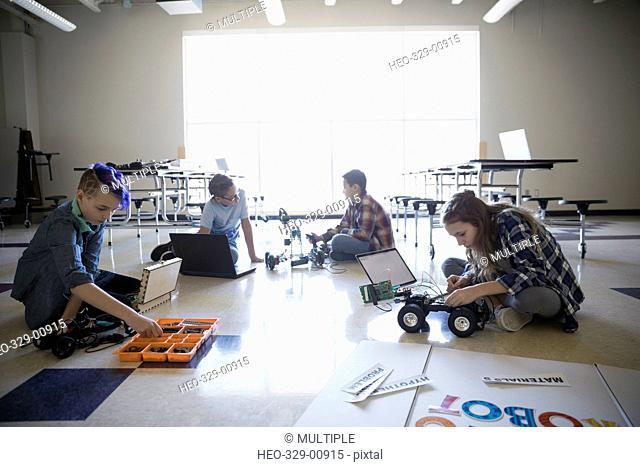 Pre-adolescent boys and girls programming robotics for science fair on classroom floor