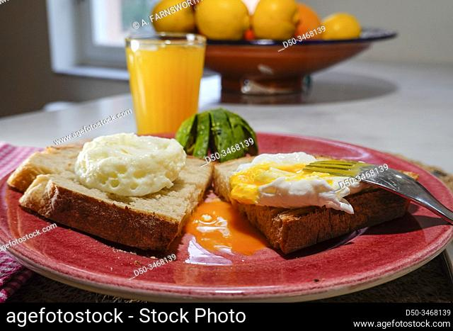 A poached egg on toast with avocado and a glass of juice