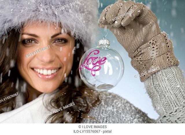 A young woman holding a glass bauble