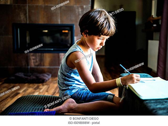 Boy kneeling on floor drawing in workbook