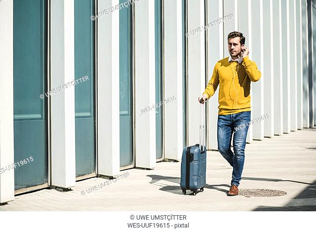Young man with rolling suitcase and earphones in the city on the go
