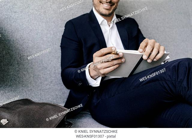 Smiling businessman with notebook on couch