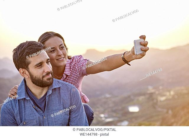 Happy, smiling young couple taking a selfie on a mountain top with a hazy natural background and wearing casual clothing