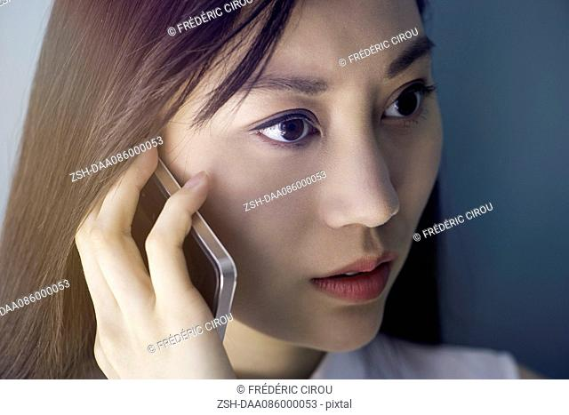 Woman listening to cell phone with serious expression