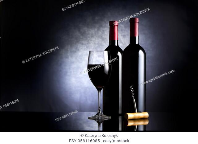 Wineglass and two bottles of wine on a black background