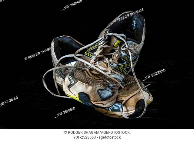 An old pair of running shoes, worn out and ready to be trashed