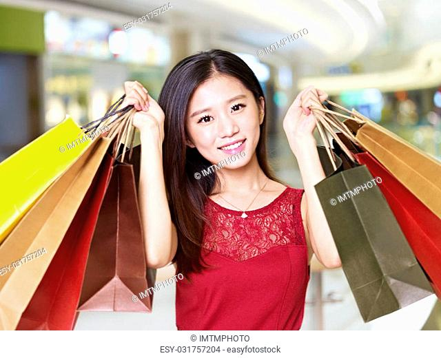 b00f1fdf338 young asian woman on shopping spree carrying paper bags walking in mall