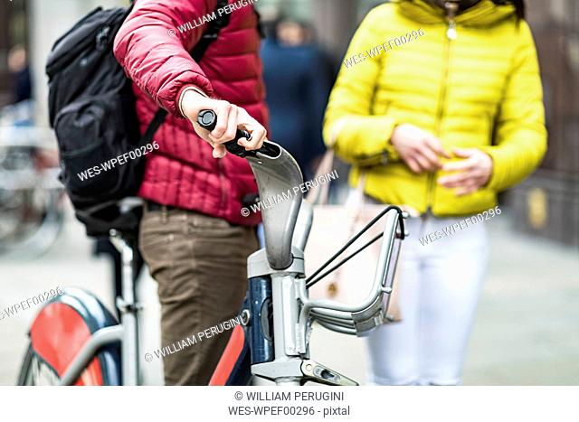 UK, London, man with rental bicycle, partial view