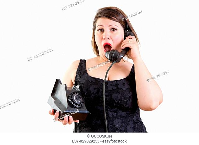 Astonished woman talking on an old fashioned rotary telephone reacting to surprising news in a communications concept on white