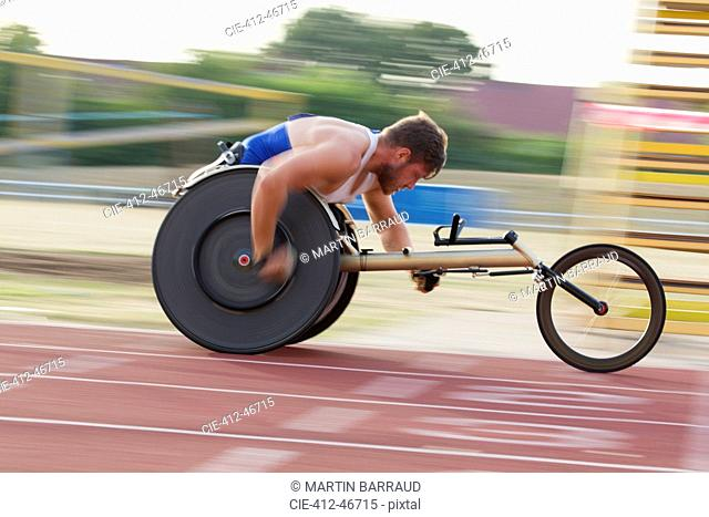Determined young male paraplegic speeding on sports track in wheelchair race