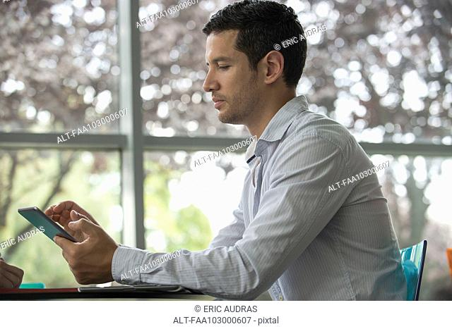 Man using digital tablet, side view