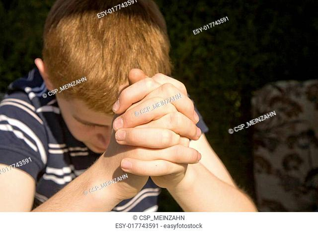 young red haired boy has his hands folded