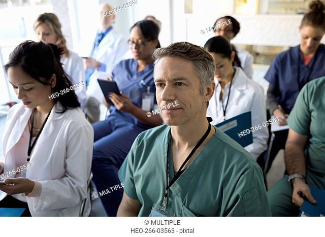 Smiling doctor listening in seminar audience