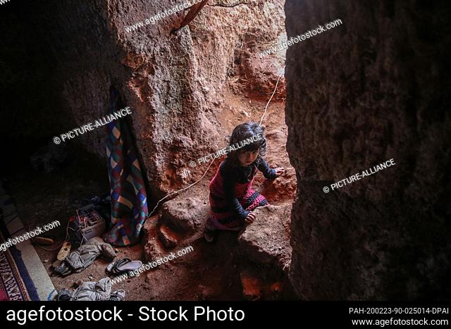 23 February 2020, Syria, Idlib: A Syrian child looks on as she sits inside a cave at Taltouna village. At least eight families live in an ancient deserted cave...