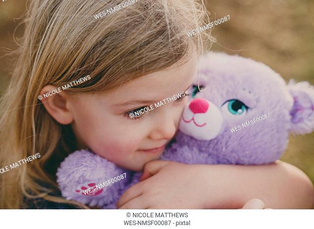 Girl cuddling a teddy
