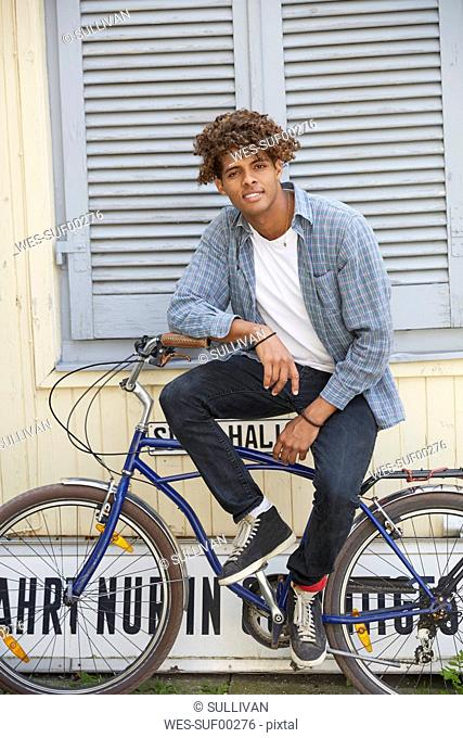 Young man sitting on bicycle, looking at camera