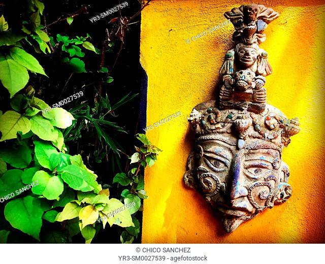 A Mayan mask decorates a yellow wall in Hacienda de Cortes, Coyoacan, Mexico City, Mexico