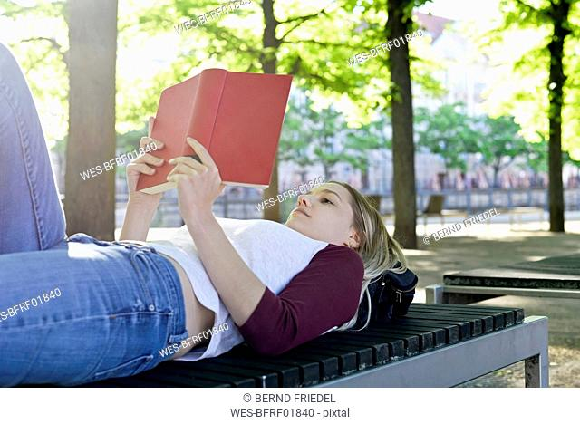 Young woman reading a book on bench