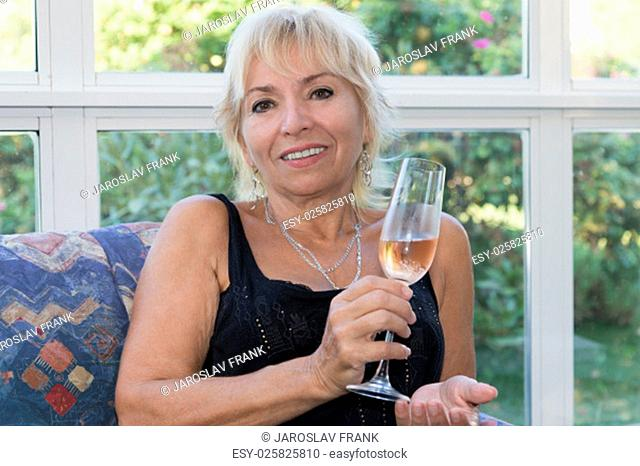 Senior mature blond woman is sitting on a couch and is smiling. She is holding a glass of champagne